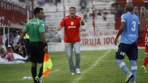 El DT tucumano reclama ante la mirada del jugador del Lobo.